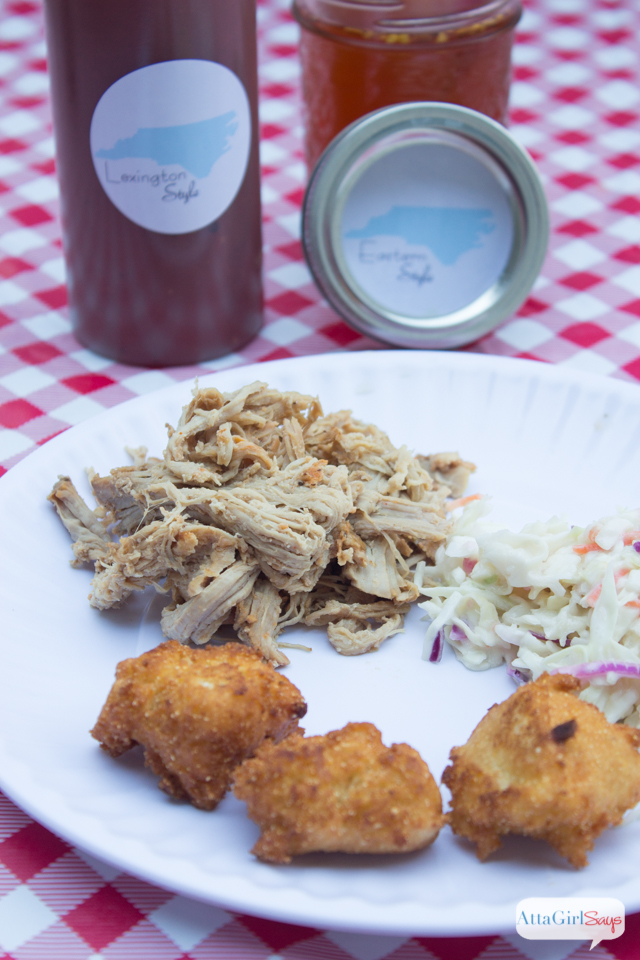 pulled pork barbeuce, hushpuppies and slaw on a white paper plate