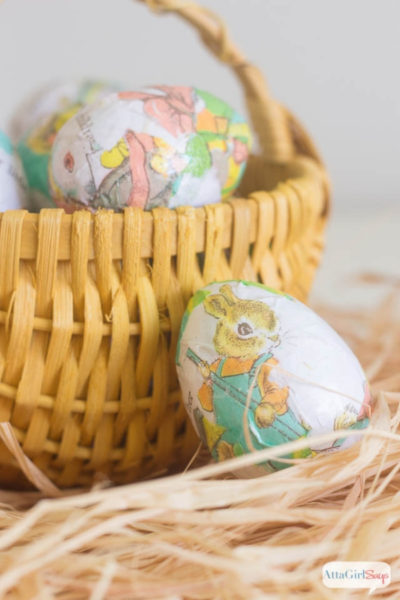 decoupaged Easter egg beside a yellow Easter basket