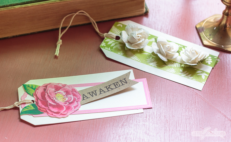 two handmade spring gift tags on a pink table