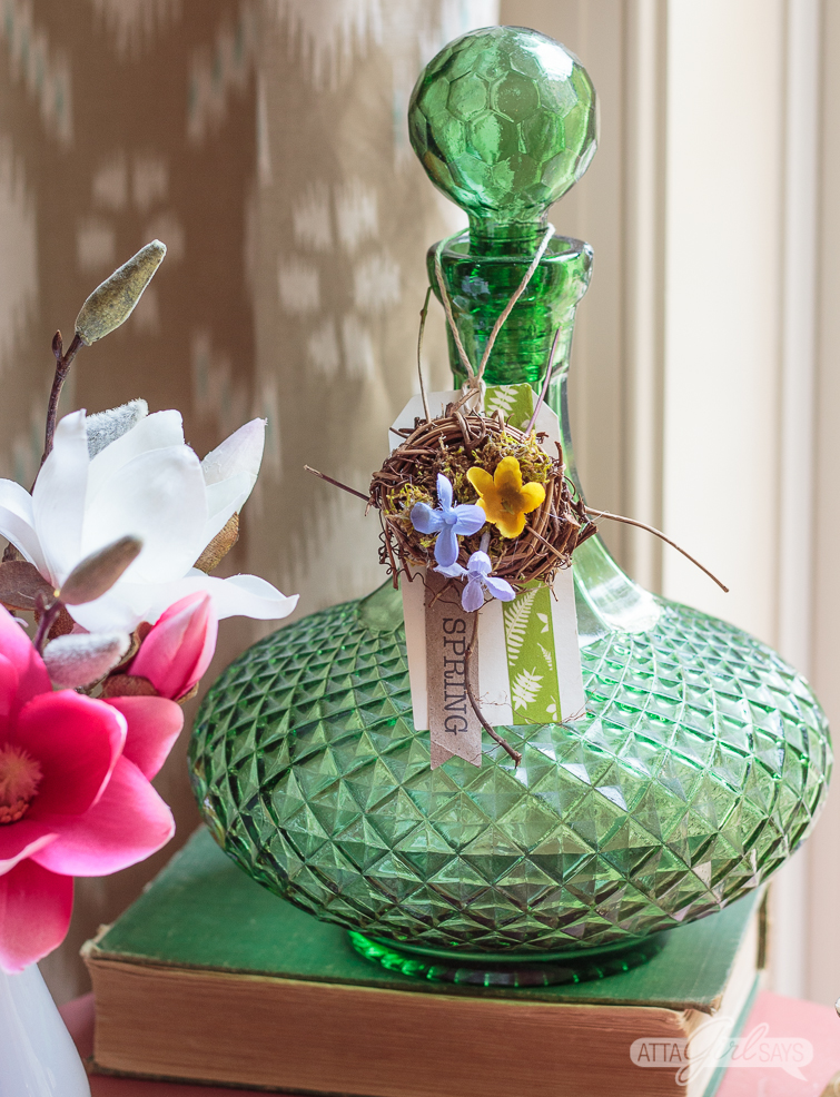 bird's nest on a spring tag hanging on a green glass bottle