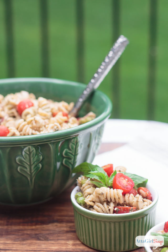 green bowl and ramekin with pesto pasta salad