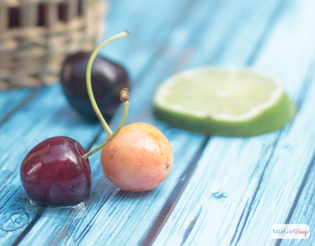 fresh cherries and a lime slice on a blue wooden table