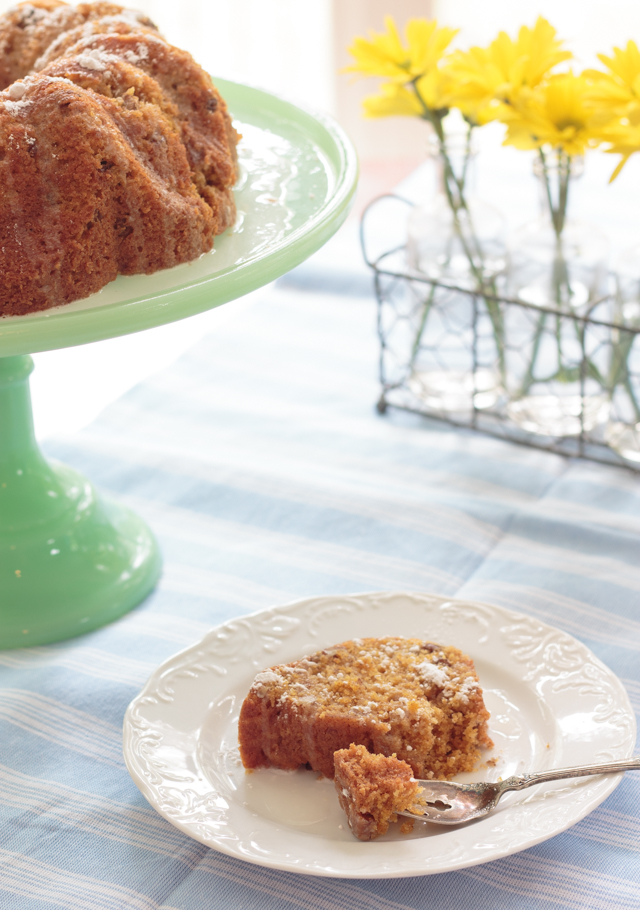 slice of carrot cake beside a cake stand with a bundt cake