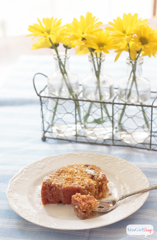 carrot cake on a table with yellow daisies in the background