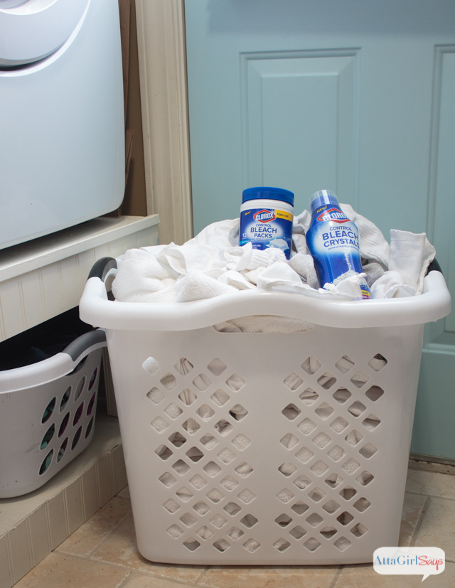 laundry basket with bleach sitting on top of it
