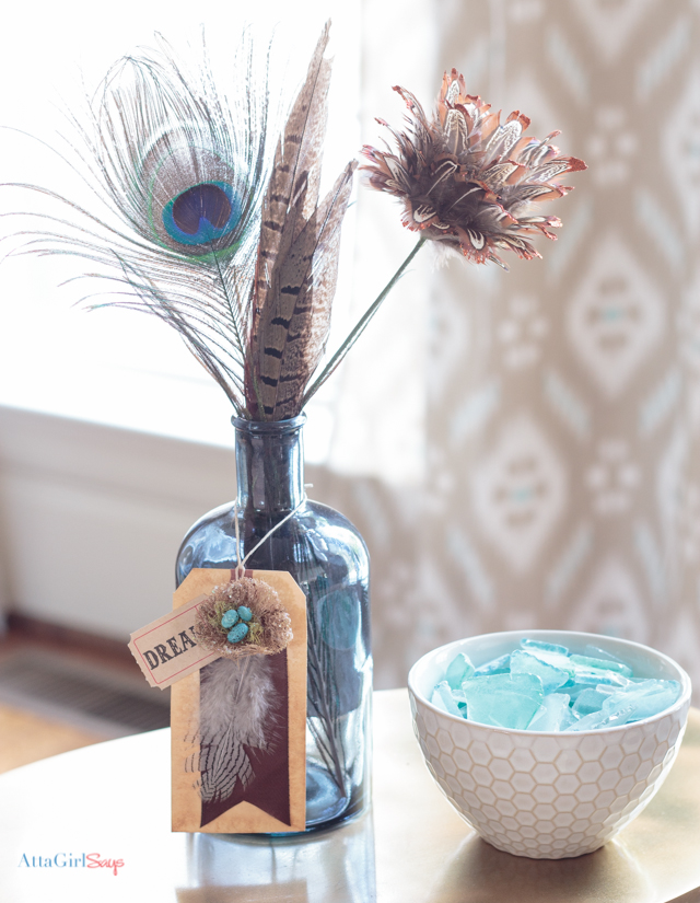 gift tag with a bird's nest hanging from a blue glass bottle