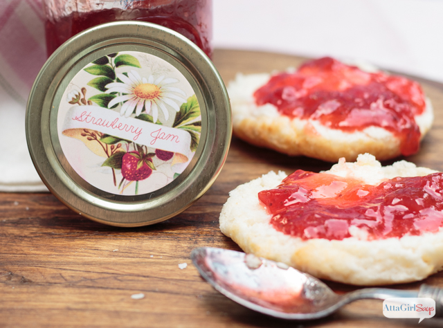 closeup of a strawberry jam jar lid with a biscuit covered with jam