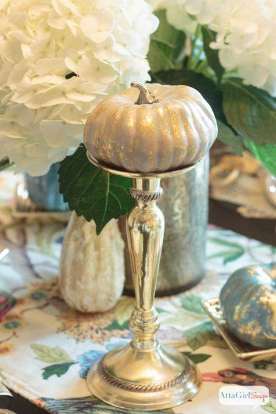 metallic painted pumpkin on a silver candlestick