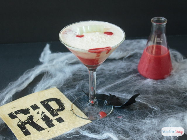These Vampire's Kiss Halloween cocktails only look sinister! But they taste delicious. Blood-red strawberry puree pierces a creamy white homemade pina colada, in this spooky take on the popular Hawaiian Lava Flow cocktail. The right garnishes and props, like vampire teeth, plastic bats, spiderwebs and a beaker filled with strawberry puree turn it into a spooky Halloween mixed drink. #ad #donthesitaste