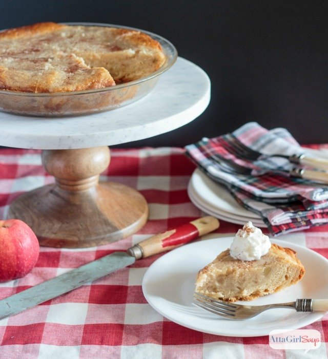 homemade applesauce pie on a marble stand with a slice cut out of it