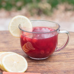 glass mug of cranberry spiced tea with lemon garnish