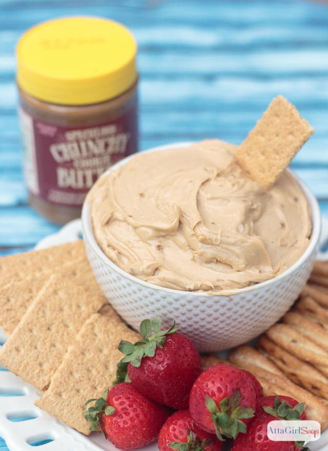 bowl of cookie butter dip on a plate with graham crackers, strawberries and pretzels
