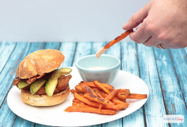 The next time you're craving fast food, give this chicken sandwich recipe a try. Fried southern-style chicken with spicy ranch sauce, bacon and avocado slices, paired with sweet potato fries with a homemade spicy boom-boom dipping sauce. #ad #farmtoflavorrecipes
