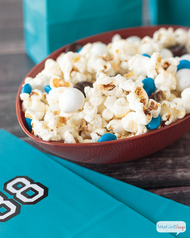 popcorn and chocolate snack mix in a football shaped bowl
