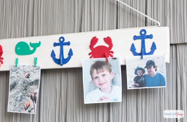 Showcase your favorite vacation memories on an inexpensive DIY picture rail made from a 1X4, wooden cutouts and mini clothespins. #decoartprojects #sponsored