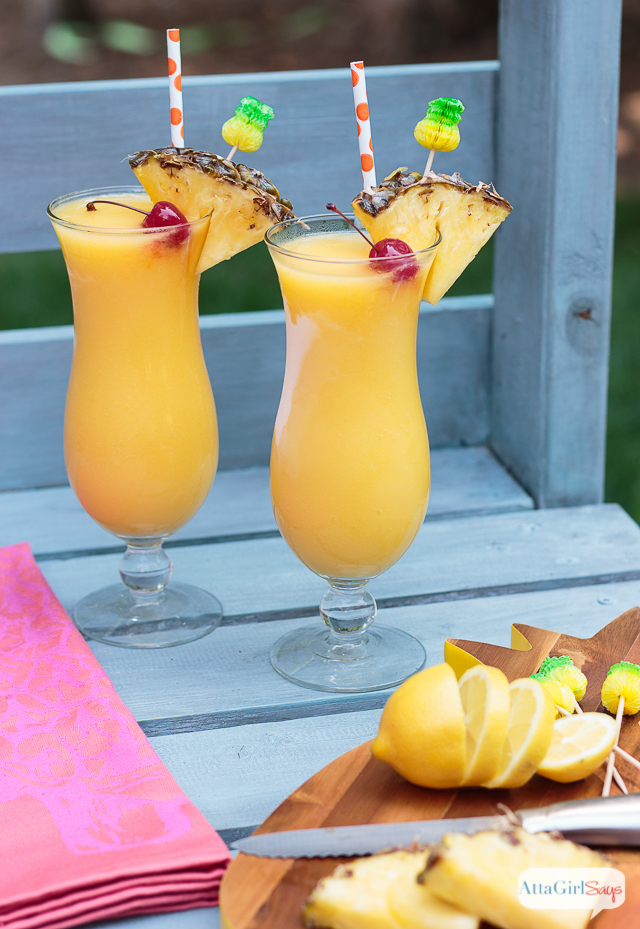 spiked frozen lemonade in a hurricane glasses with pineapple and cherry garnish