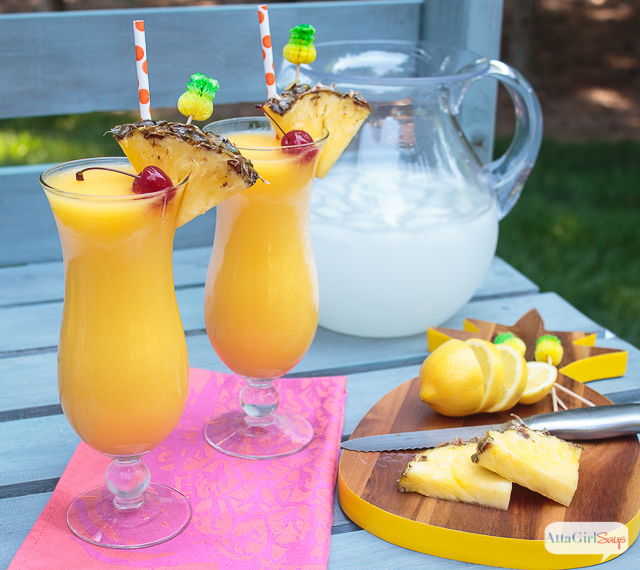 Frozen spiked tropical mango lemonade in hurricane glasses beside a pineapple cutting board and a pitcher of lemonade