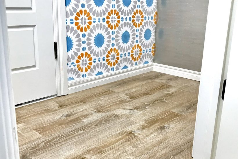 laundry room with orange and blue tile walls and gray vinyl floors