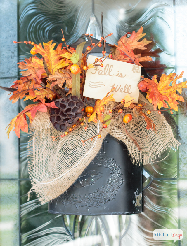 Think beyond the traditional wreath as you're planning your fall door decor. Here, a farmhouse style vintage mailbox holds an arrangement of seasonal florals.