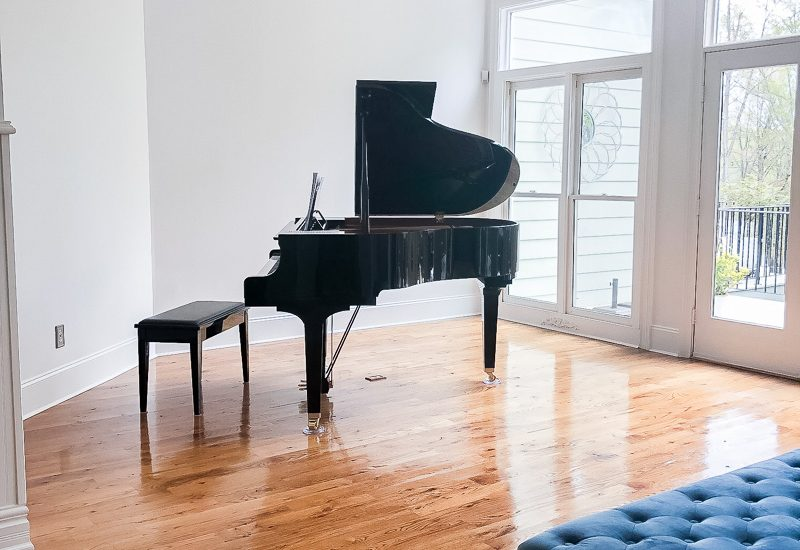 grand piano on gleaming hardwood floors in a music room