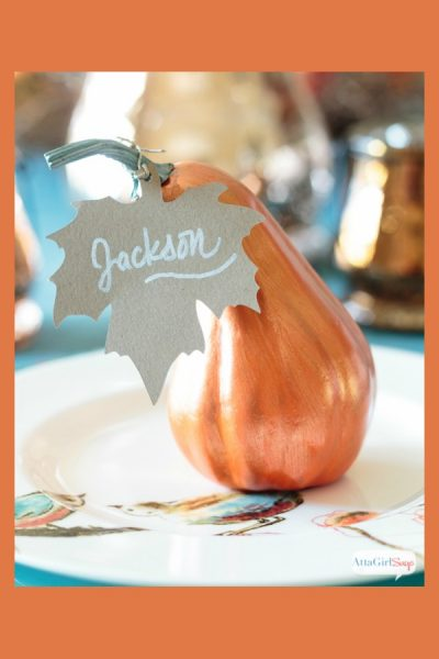 painted gourd with a paper leaf place card on a Thanksgiving table