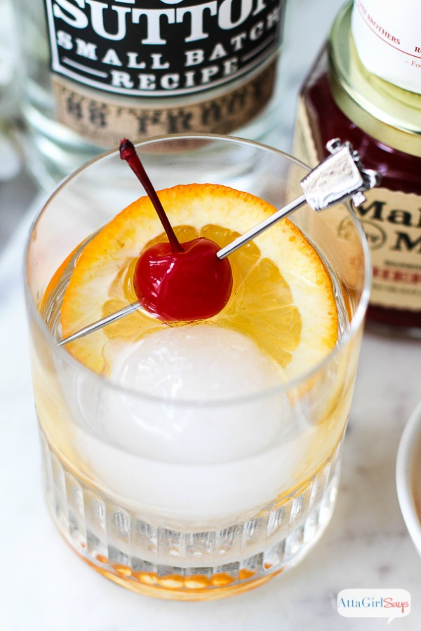 moonshine old fashioned with a round ice cube and cherry and orange garnish