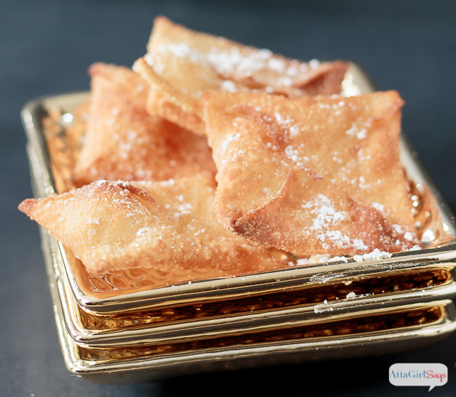 closeup of fried wonton envelopes dusted with powdered sugar