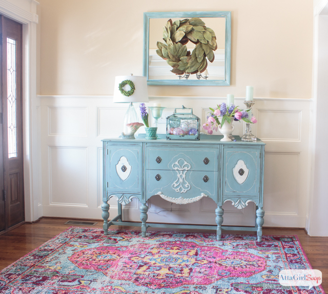 traditional foyer with an aqua blue painted buffet on a pink and aqua rug with vintage pink and aqua pottery an spring flowers