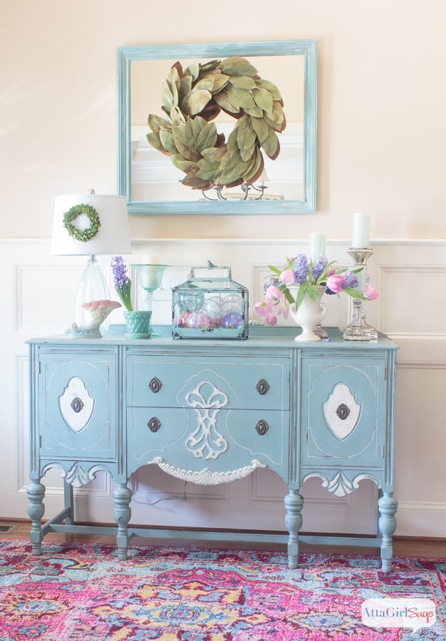 colorful spring foyer with a pink rug and a blue buffet