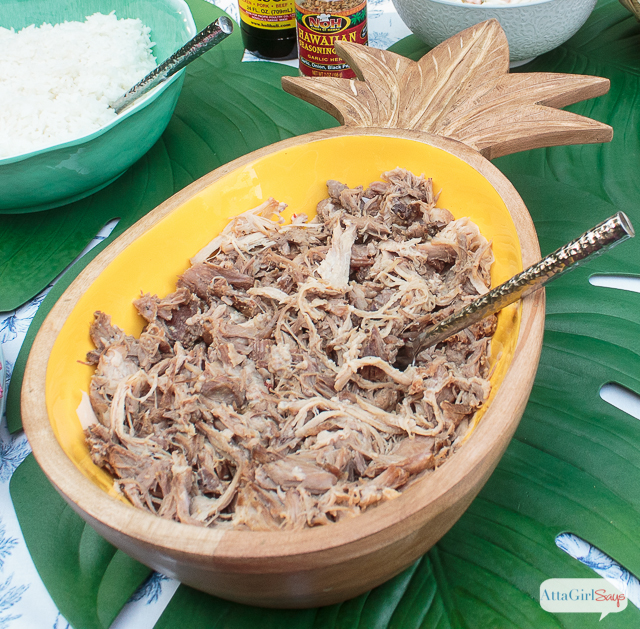 Kalua pork in a pineapple bowl on top of a monstera leaf