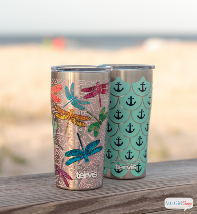 A pair of Tervis stainless steel tumblers sitting on a wooden deck railing overlooking a sandy beach. One cup features a colorful dragonfly design, while the other is decorated with navy blue anchors on an aqua scalloped pattern. #sponsored