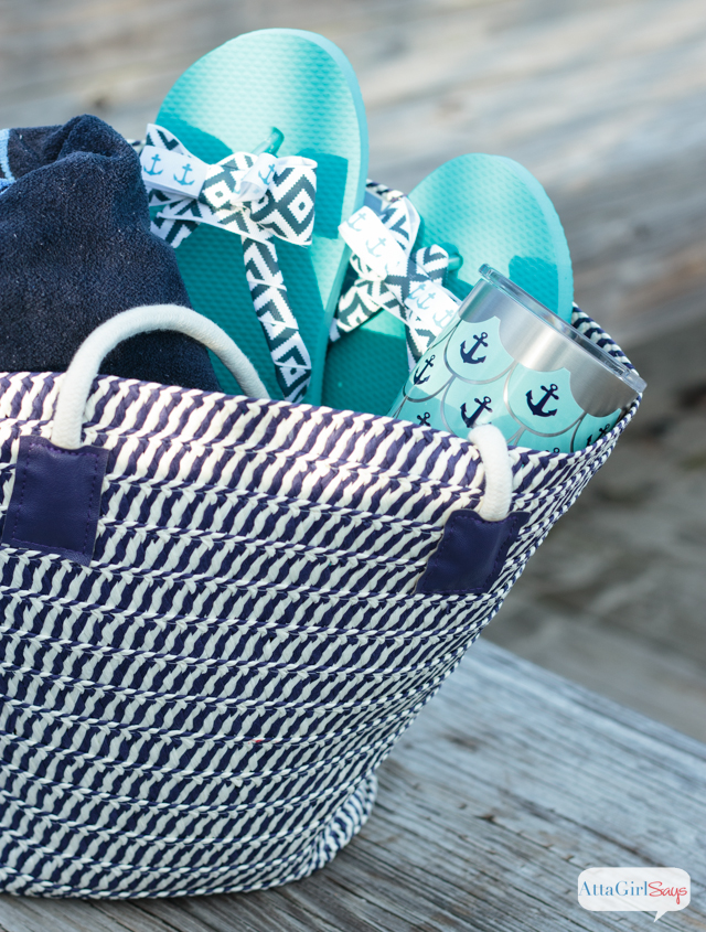 A straw beach bag packed with a navy blue towel, a pair of DIY bow flip flops and an insulated stainless steel Tervis tumbler with an aqua and blue anchor pattern on it. #sponsored