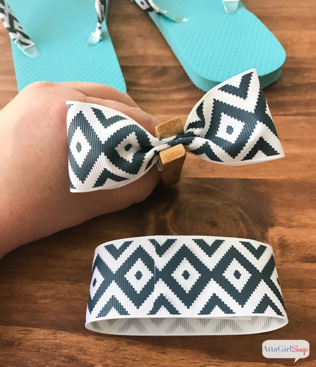 Step 5 to make DIY bow flip flops: Once the loops have dried, pinch the center into a bowl shape, and apply glue to the pleats. Use a clothespin to hold the bow shape while the glue dries. Repeat with the smaller ribbon. Allow all bows to dry completely. #sponsored