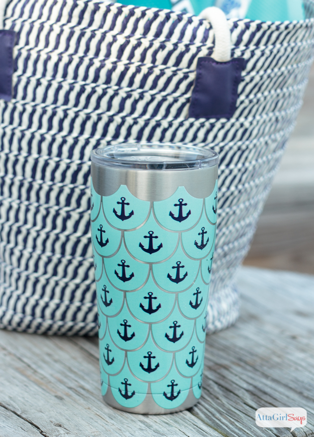 Closeup of a Tervis stainless steel tumbler with an anchor design, sitting next to a straw beach bag on a weathered wooden table with the beach in the background. #sponsored
