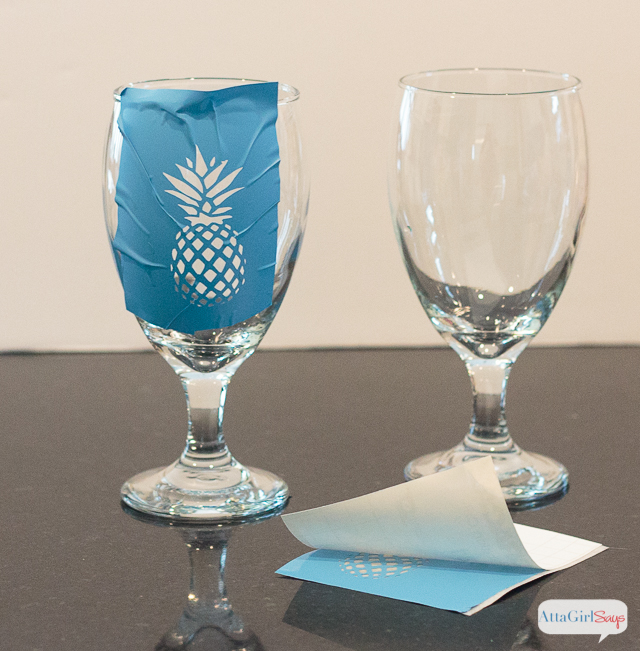 To make the etched pineapple drinking glasses, use a Silhouette cameo to cut a pineapple stencil from vinyl. Apply the adhesive stencil to the water goblets, pressing firmly