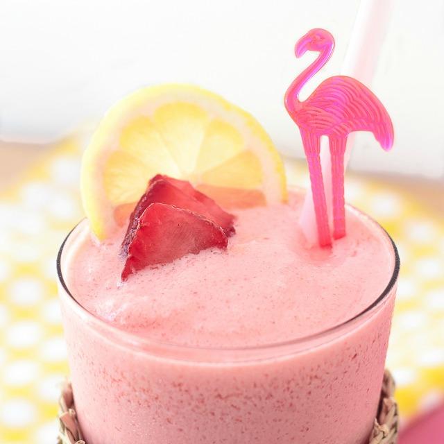 glass of frozen strawberry lemonade garnished with a lemon slice and a flamingo swizzle stick