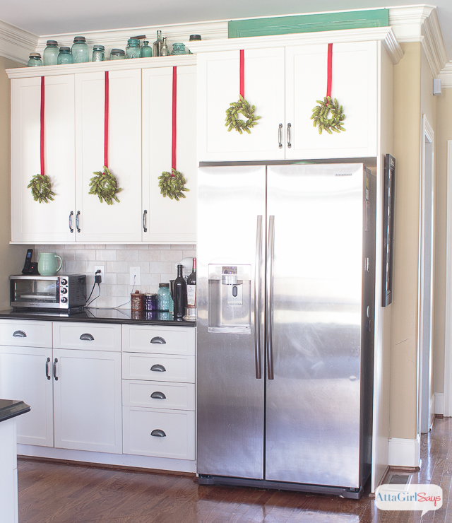 stainless steel refrigerator in a kitchen with black granite countertops and white cabinets
