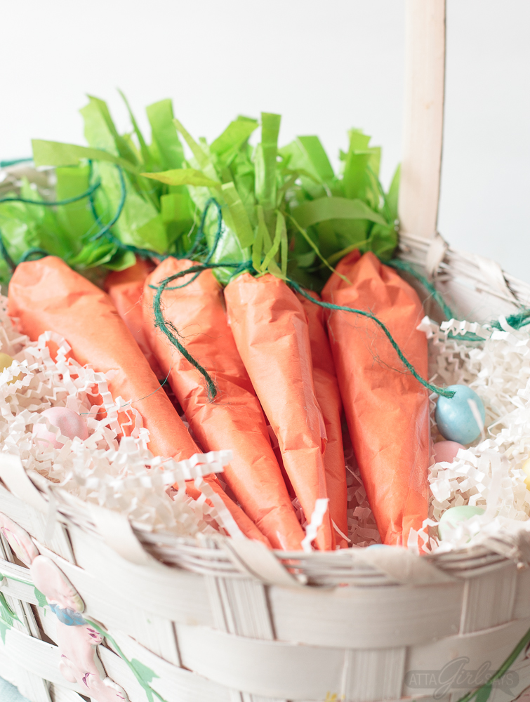 These tissue paper carrots hide a tasty surprise inside. Fill them with miniature chocolate eggs, jelly beans, M&M's or another favorite Easter candy. Click for step-by-step instructions, plus a supply list to make this adorable, edible Easter basket craft. #Easter #tissuepaper #carrots #eastercrafts