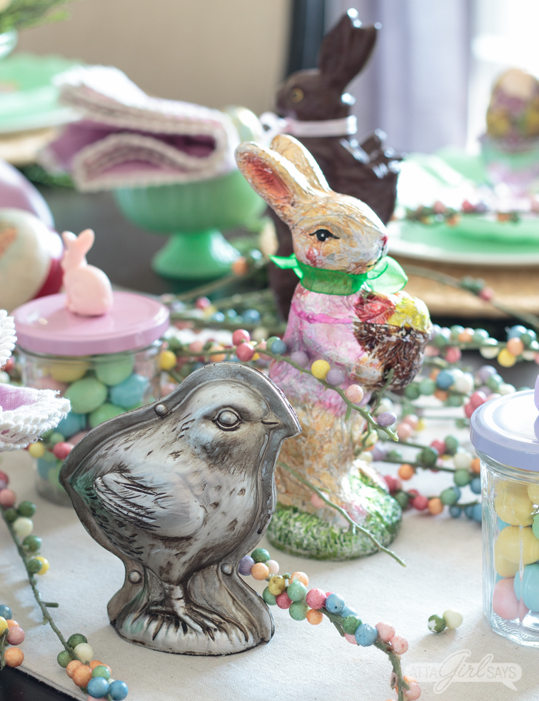 Let this pretty holiday tablescape, featuring pops of pastel and candy, inspire your own Easter table decor. I used chocolate molds, pastel candies, vintage Easter eggs and chocolate bunny figurines to create this sweet seasonal scene. #eastercandy #tablescape #eastertable #springtablescape #tabledecor