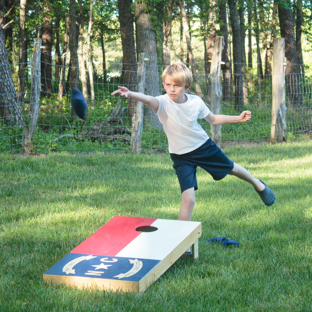 Blonde boy tossing a cornhole beanbag while playing on North Carolina state flag cornhole boards