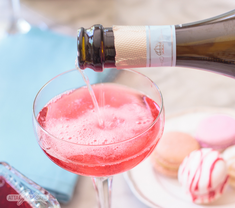 Pouring La Marca Prosecco into a coupe glass to make a pink blooming hibiscus cocktail. This is such a fun drink to make at your next brunch! Click for the recipe + 2 more versions. #ad #CelebratorySips #CelebrateWithLaMarca
