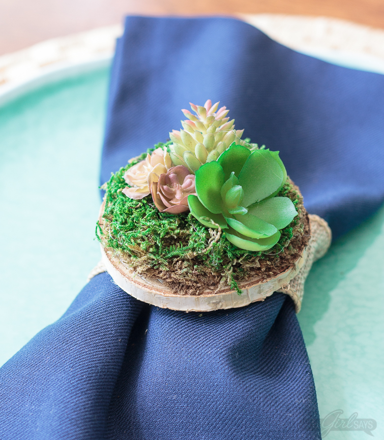Miniature succulent garden on a mossy wooden napkin ring, atop a sea blue plate