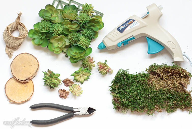 A collection of supplies required to make a DIY succulent napkin ring. The photo shows a glue gun, sheet moss, faux succulent plants, wire cutters, birch wooden round coasters and burlap jute ribbon.