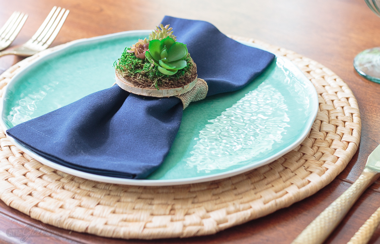Dinner place setting featuring an aqua blue plate on a woven natural charger. A miniature succulent garden napkin ring holds a navy blue napkin