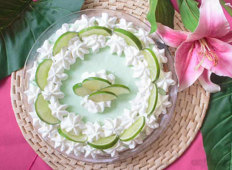 frozen margarita ice cream pie garnished with limes and lily flowers