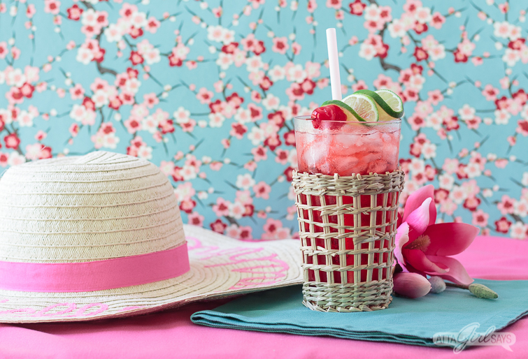 summer straw hat sitting beside a sparkling cherry vodka cocktail