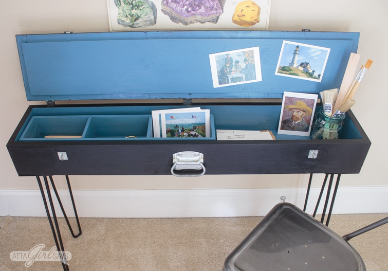 Interior of a hairpin leg desk, painted a bright French blue. The desk is filled with postcards, envelopes, pencils and other art and writing supplies.