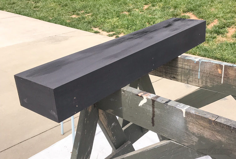 Long wooden box, painted black, on sawhorses.