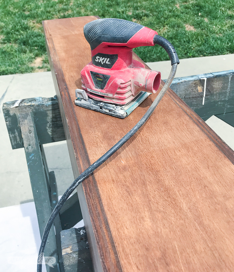 Sanding the top of a long wooden boxtop to remove adhesive residue and prime for painting.