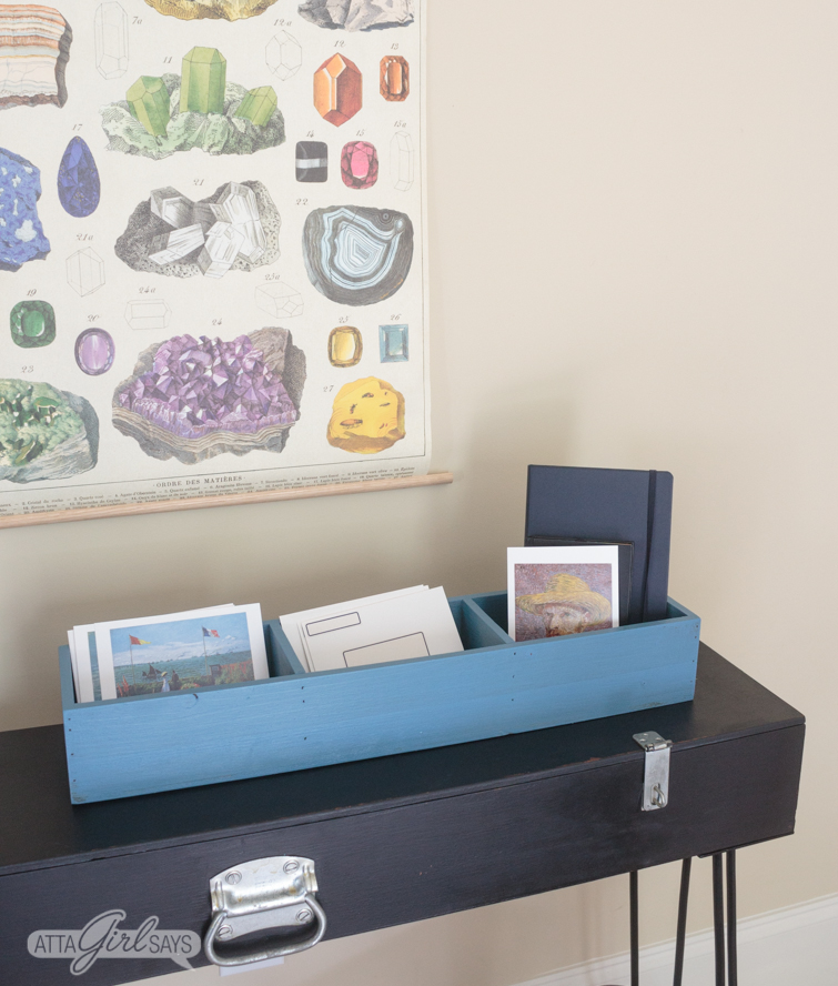 Black hairpin leg desk with a blue storage box on top of it.